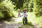 Toddler boy riding bike on dirt path. Toddler boy riding bike on dirt path