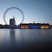 London Eye and building by still river. London Eye and building by still river