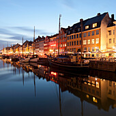 Apartments on canal lit up at night. Nyhavn, Copenhagen, Denmark