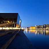 Lit buildings reflected in urban canal. Left: Royal Danish Library Det Kongelige Bibliotek, Black Diamond building, Copenhagen, Denmark