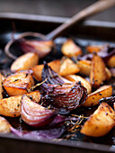 Close up of roasted vegetables in tray. Balsamic Roast Potatoes withRed Onions & Rosemary