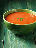 Close up of bowl of tomato soup. Tomato Soup in green bowl with a herb garnish