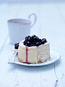 Plate of blackcurrant cheesecake. Blackcurrant Cheesecake with a cup of tea