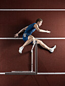 Runner laying with hurdle on track. Athlete jumping over hurdle, lying on track and field stadium