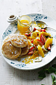 Plate of pancakes with fruit salad. PikeletsMangoSalad