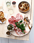 Plate of sliced meats, bread and herbs. CharcuteriePlateOnions