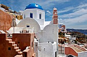 Blue domed church and salmon-colored deck overlooking ocean in the village of Oia in Santorini, Greece