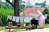 Woman washing linen in Old Salem Moravian religious community founded 1766, in modern city of Winston Salem, North Carolina, USA