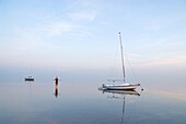 Woman standing among sailboats in Wadden Sea at sunset, Juist, Germany