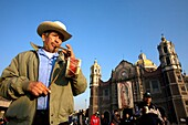 A musician plays a flute and a drum outside the Our Lady of Guadalupe Basilica in Mexico City, December 11, 2007  Millions of Mexican pilgrims converged on the Basilica, bringing images to be blessed, as processions filled the streets for the feast day of