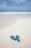 Tropical beach on the Island of Barbados with sandals left on the beach and someone swimming in the Caribbean.