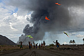 Children playing with kites amongst the volcanic ash, Tavurvur Volcano, Rabaul, East New Britain, Papua New Guinea, Pacific