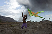 Children playing with kites in the volcanic ash, Tavurvur Volcano, Rabaul, East New Britain, Papua New Guinea, Pacific