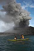 Auf dem Weg zur Arbeit. Männer paddeln von Matupi zum Vulkan, um Eier zu suchen, Tavurvur Vulkan bei Tag, Rabaul, Ost-Neubritannien, Papua Neuguinea, Pazifik
