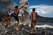 Happy children playing in the sea, Tavurvur Volcano, Rabaul, East New Britain, Papua New Guinea, Melanesia- Pacific