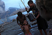 The children on Matupit Island have only contaminated acid water to wash themselves, Tavurvur Volcano, Rabaul, East New Britain, Papua New Guinea, Pacific