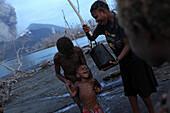 Kinder auf der Insel Matupit können sich nur mit verseuchtem Wasser waschen, Tavurvur Vulkan, Rabaul, Ost-Neubritannien, Papua Neuguinea, Pazifik