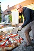 Man with pizza on a bread shovel, Klein Thurow, Roggendorf, Mecklenburg-Western Pomerania, Germany