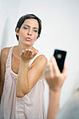 Woman blowing kiss in a mobile phone