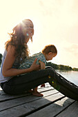 Woman with small child, sitting on wooden pier, old danube, Vienna, Austria