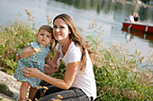 Young mother with daughter at Danube riverbank, Old Danube, Vienna, Austria