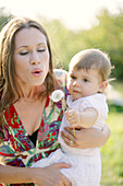 Young mother with her daugther, blowing dandelion clock, Old Danube, Vienna, Austria