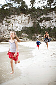 Frau und zwei Mädchen laufen am Strand entlang, Cala de s Almunia, Santanyi, Mallorca, Balearen, Spanien
