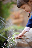 Girl holding finger in water jet, museum La Granja, Esporles, Majorca, Balearic Islands, Spain
