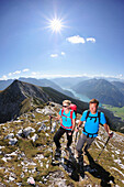 Young woman and young man hiking on ridge, Lake Achen in background, Unnutz, Brandenberg  Alps, Tyrol, Austria