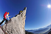 Young woman belaying climber at pinnacle, Kampenwand, Chiemgau Alps, Chiemgau, Upper Bavaria, Bavaria, Germany