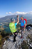Young woman and young man reaching summit at fixed rope route Rino Pisetta, Lago die Toblino, Sarche, Calavino, Trentino, Trentino-Alto Adige, Suedtirol, Italy