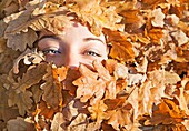 Portrait of a woman covered form leafes in Park in Autumn
