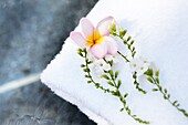White towel with tropical flowers at the edge of a basin