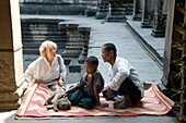 Asia, Cambodia,  Siem Reap , Angkor Wat, woman tourist with father his son and monkey seated on a carpet in courtyard of temple.