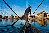 Myanmar (Burma), Shan State, Inle lake, Intha fishermen have created an unique way to move on the water : standing up on a leg at the back of a canoe, they lean the other on a stick that they guide with their ankle, the foot behind, thanks to their keepne
