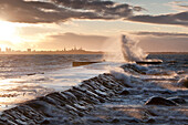 A weather storm, creating  waves crashing over the Pier and coastline in Tallinn, Estonia. The Baltic Sea. Sunrise., Tallinn coastline and stormy seas