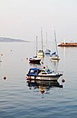View out to sea on the English coastline, with  flat calm water. Sea wall, Sheltered mooring. Yachts and motor boats at anchor. Headland., Boats in a sheltered harbour