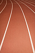 The surface of a sports ahtletics running track in Thousand Oaks, California, USA. Red surface with white painted lane markings. Curve of a bend., Lanes of running track
