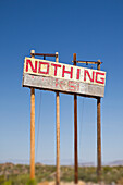 A tall road sign, in a flat dry arid landscape., Nothing Sign, Nothing, Arizona, USA