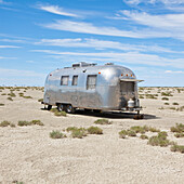 Vintage Airstream trailer on Bonneville Salt Flats, photographed during Speed Week, an annual amateur auto racing event in Utah, USA. Caravan, silver exterior., Vintage Airstream trailer in desert
