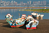 Small fishing boats on the beach. Nets and fishing gear. flat calm water, estuary. Coastline. Cityscape of Taipei city, Taiwan, Asia., City beach and boats