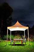 A small gazebo in a garden. Tent shape covering, over a table and seta. Space for working at night in the garden. Darkness. Silhouette of trees. Shrubs., Taoyuan county, Taiwan, Asia.