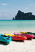 A tourist destination and resort in the Andaman islands off the cost of Thailand. A view out to sea from the white sand beach. Kayaks for hire on the beach. Rocky headland, and limestone karsts rising from the water., Ko Phi Phi Island, Krabi Province, Th
