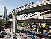 A mass transit train travelling on an elevated track above the city road. Traffic. Cars and buses on the multilane highway below. Urban scene., Bangkok, Thailand. Traffic and transport.