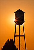 Sun setting behind agricultural water tower, Willamette Valley, Oregon, USA, Sunset and an agricultural water storage tower