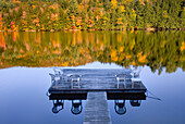A  private dock on a calm lake, in the fall. Autumn. Trees with turning leaves. Amherst Lake. Flat calm water and a mirror reflection., Amherst Lake, Vermont, USA.