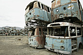 The effect of the conflict in Afghanistan. Stacked ruined buses and trams from the transport system, in a scrap yard., Kabul, Afghanistan