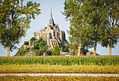 A view of Le Mont Saint-Michel. Historic monument and UNESCO world heritage site on a rocky outcrop on the mud flats off the coast of Normandy. A cathedral with a tall spire. An international landmark. Farmland onthe coast., Le Mont Saint-Michel, Normandy