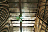 Simple iron roof of warehouse with a electric fan for ventilating, Taiwan, Asia.