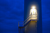 The light above the maintenance door illuminating the staircase on the side of the central mast of a wind turbine. Night. Wind power generation., Wind Turbine Maintenance entrance